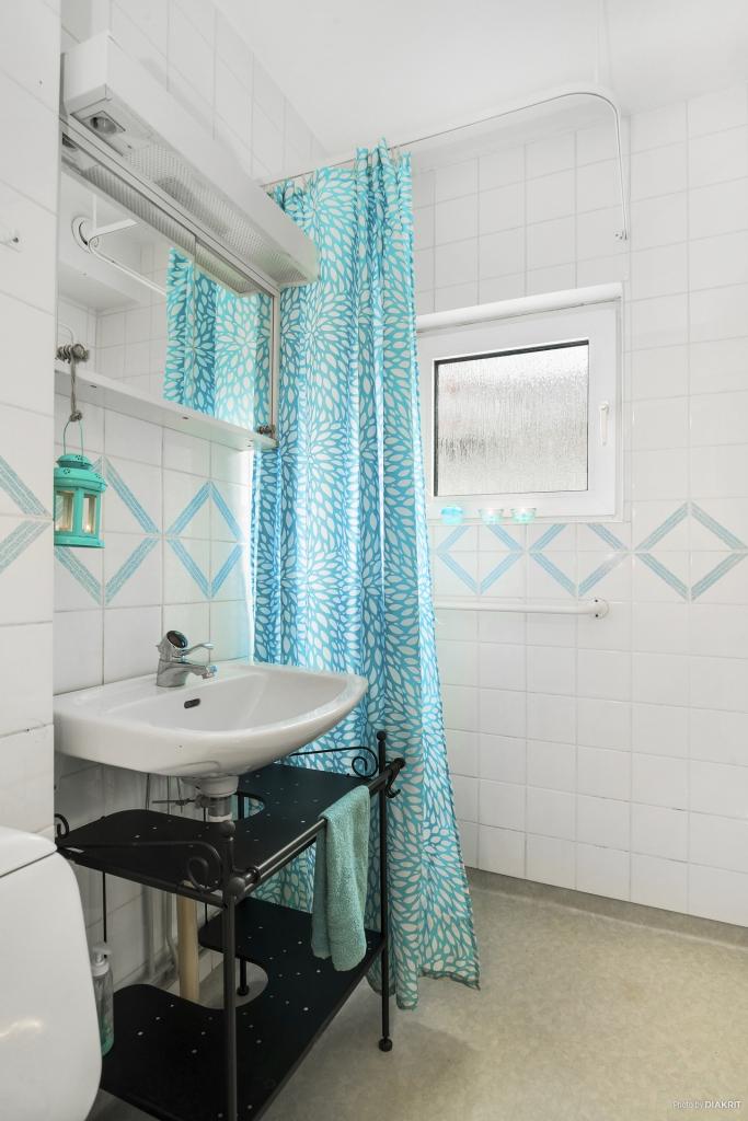 Badrum med duschhörna och fönster.