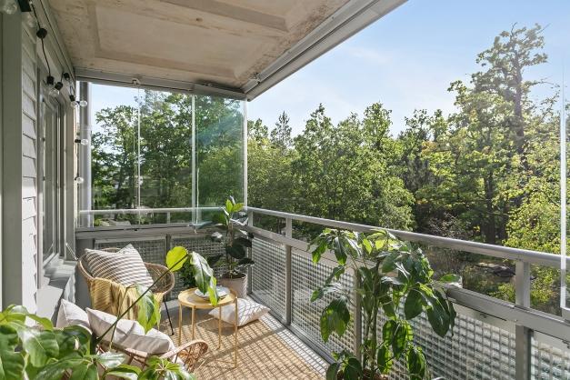 13 kvm stor, inglasad balkong mot solen och grönskan utanför