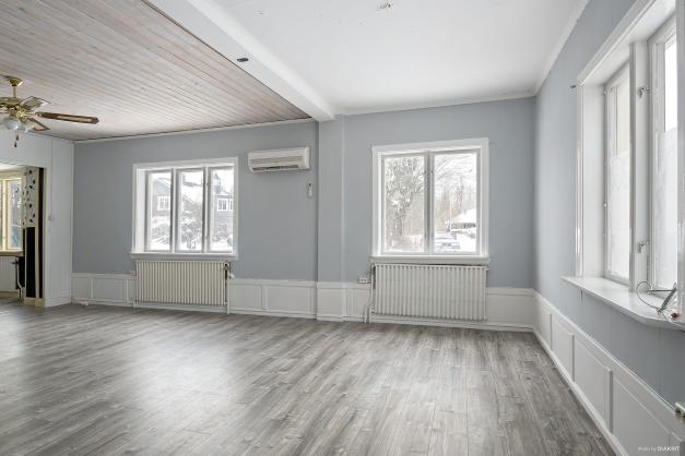 Vardagsrum med fönster i flera väderstreck med vacker vitmålad och tidsenlig bröstning