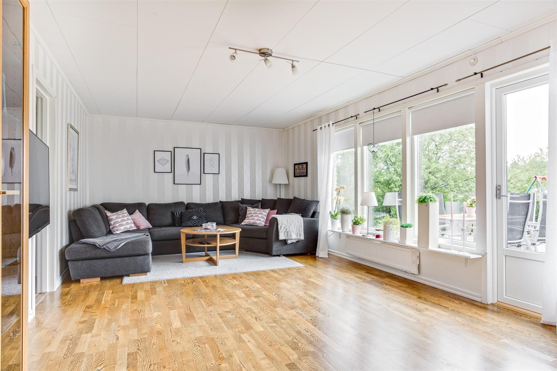 Vardagsrum med fint parkettgolv och stora fönster som ger fint ljus.