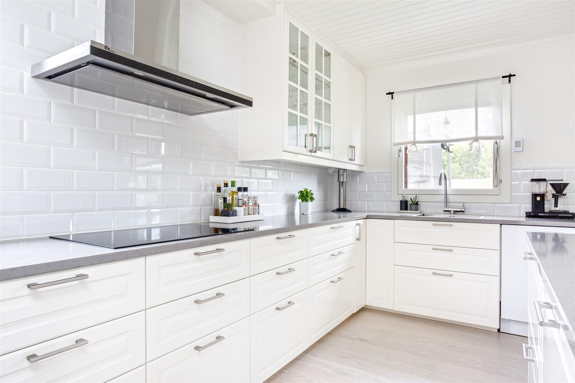 Köket har vita köksluckor från IKEA, bänkskiva i grå sten och vitt kakel över arbetsbänken.