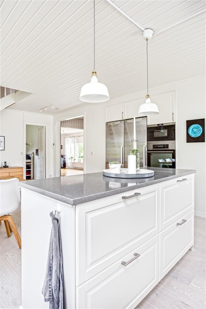 Köket har en praktisk köksö med bänkskiva i grå sten med belysning över.