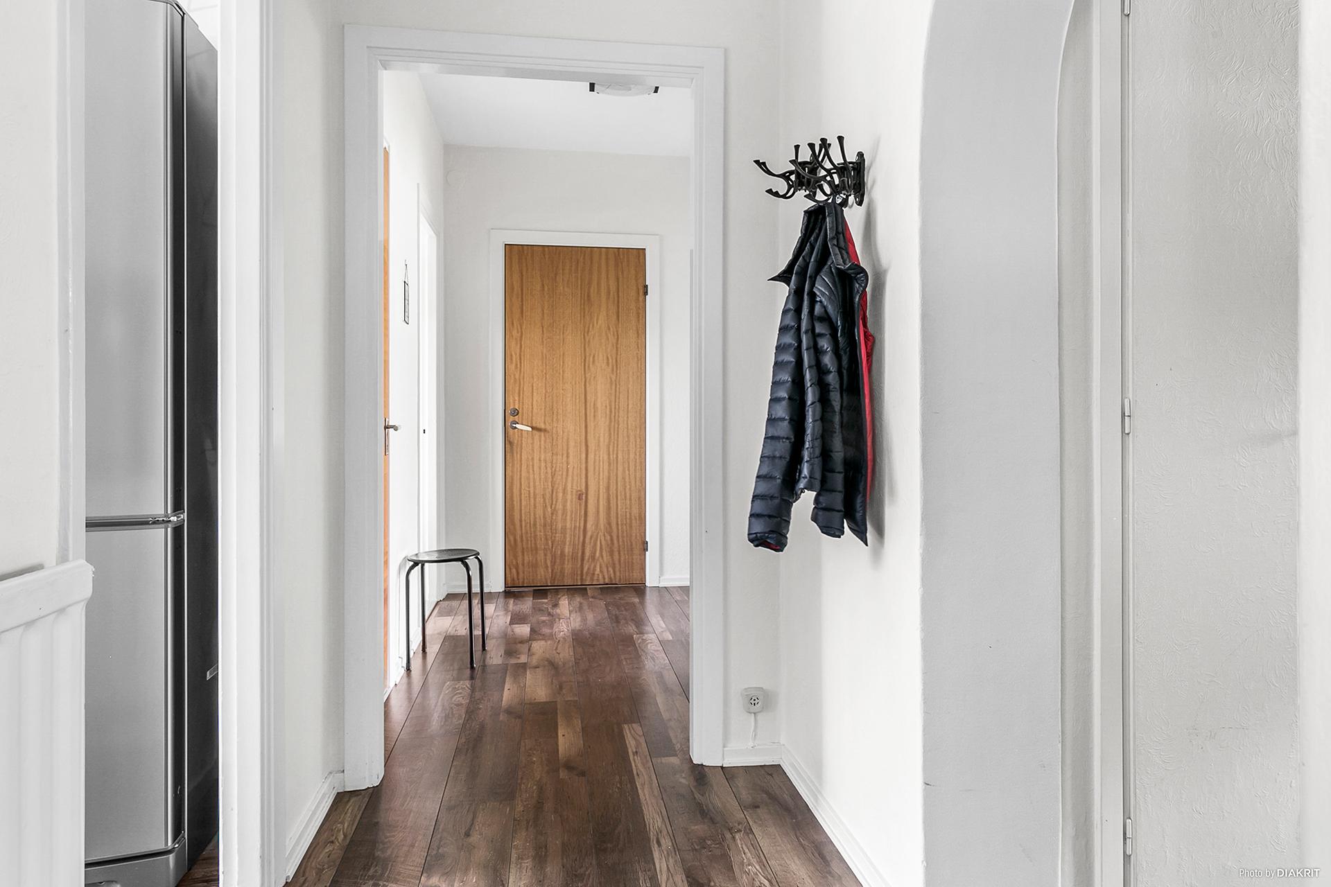Hall med vita väggar och mörkt golv