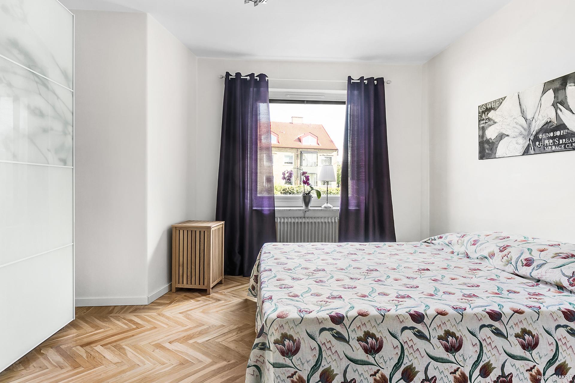 Ett stort sovrum med fiskbensparkett och skjutgarderob