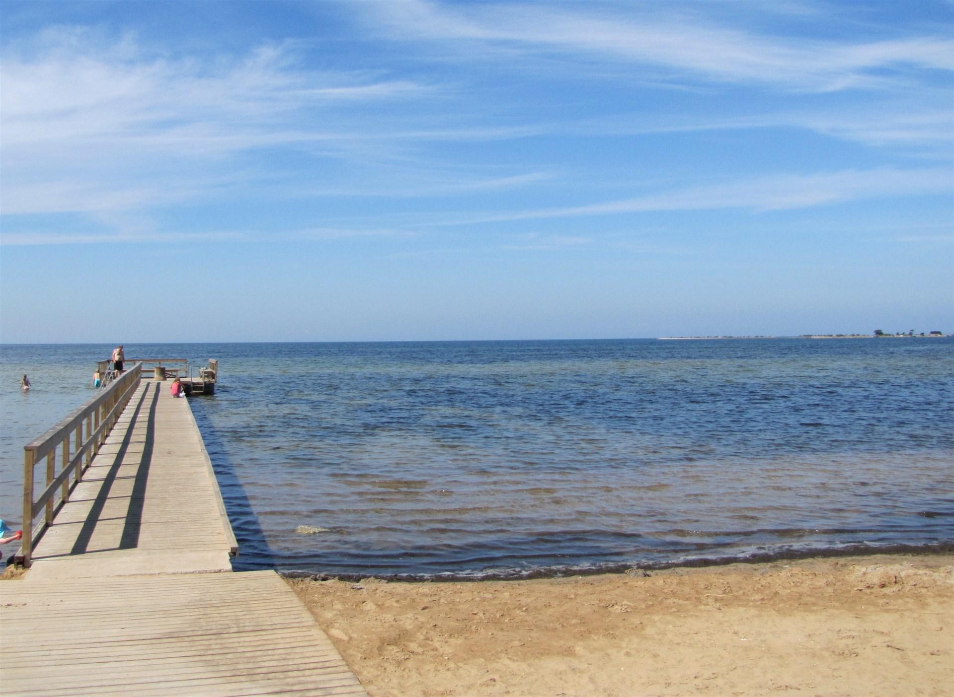 Fin sandstrand och brygga inom promenadavstånd