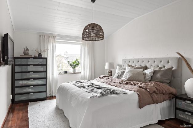 Stor och ljust sovrum med plats för dubbelsäng och byrå.