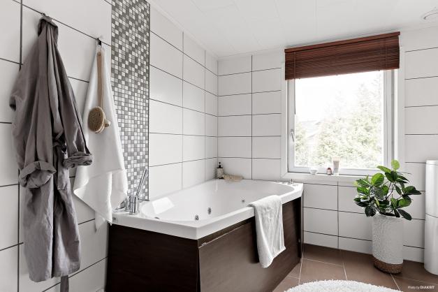 Helkaklat och stort badrum inrett med badkar, handfat med kommod och spegel samt toalett.