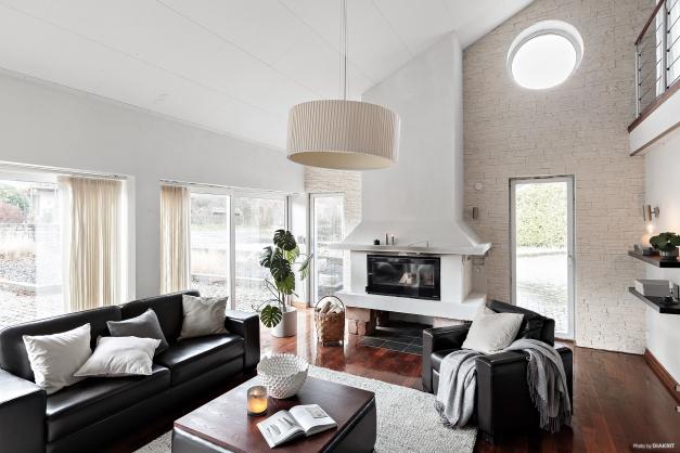 Vardagsrummet har stora fönsterpartier och generös takhöjd!