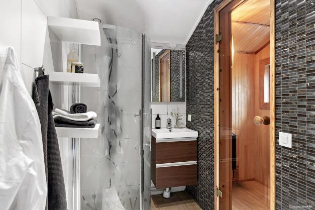 Helkaklat och fräscht badrum med ingång till bastun.