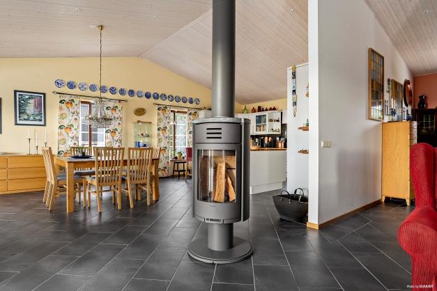 Braskaminen utgör en naturlig mittpunkt mellan kök och vardagsrum