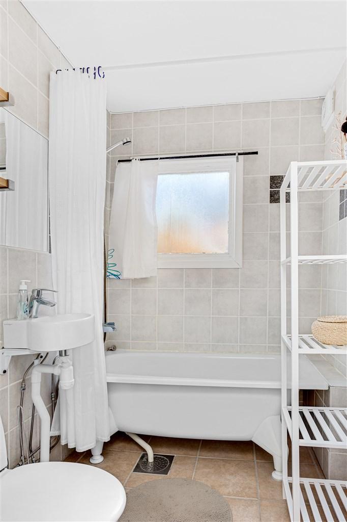 Badrum med badkar, wc och handfat. Badrummet har kakel på vägg och klinker på golv.