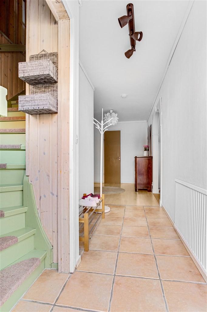 Välkommen in, hall med klinkergolv. Här finns uppgång till övervåningen.