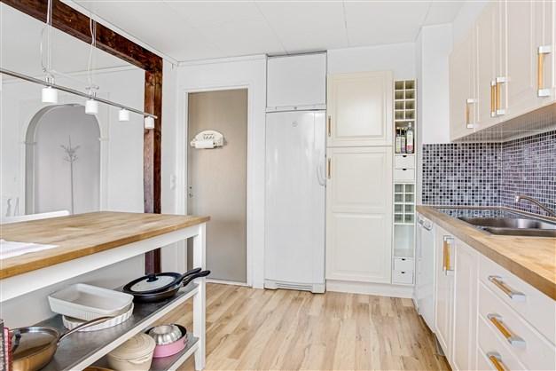 Köket har en vinhylla och en köksö.