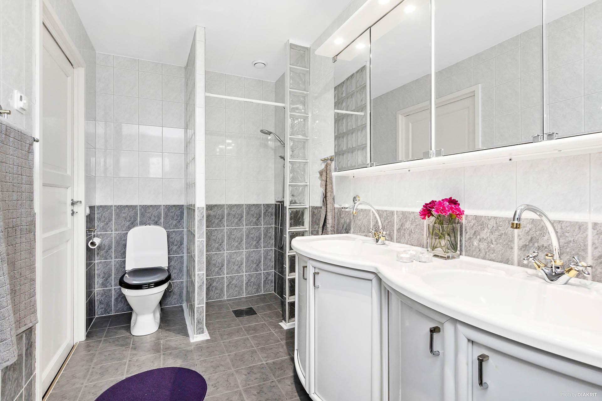 Rymligt badrum med dubbla handfat och dusch.