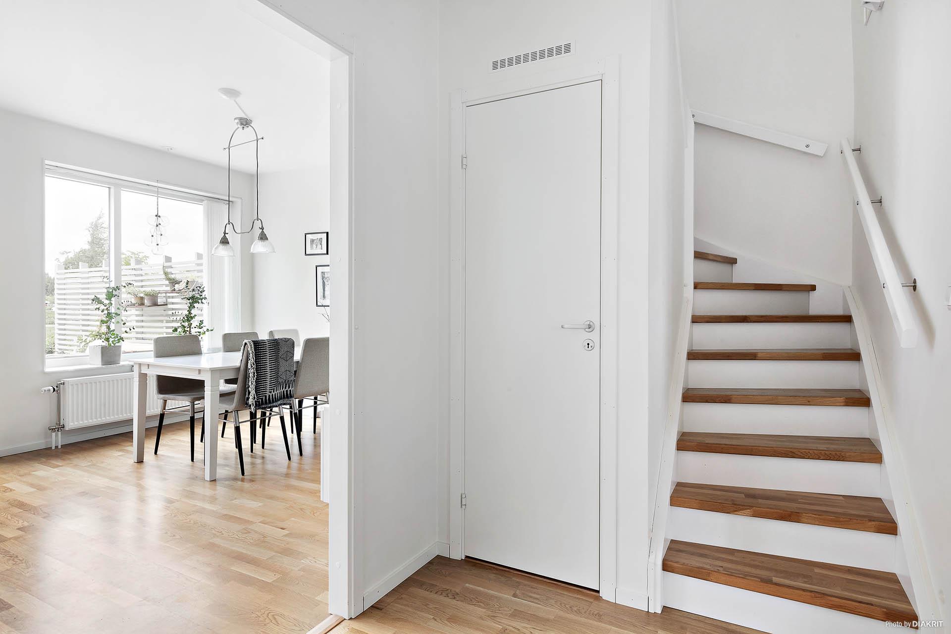 Hall med trappa till övervåning. Förråd under trapp.