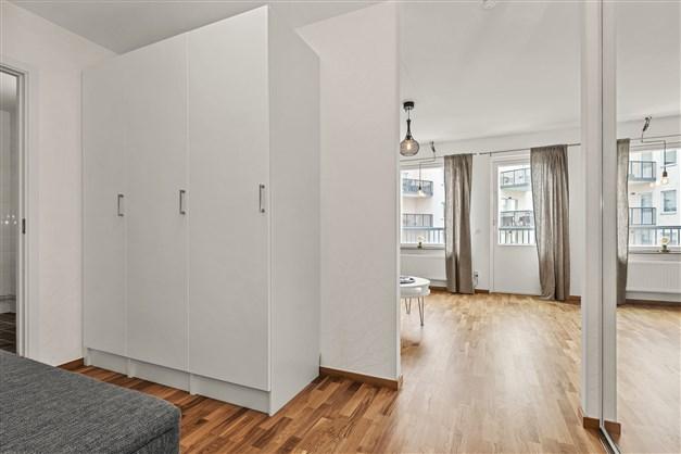 Välkomnande hall med tre garderober/städskåp samt garderob bakom skjutdörrar med spegelglas