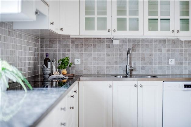 Ljust kök med delvis vitrinskåp