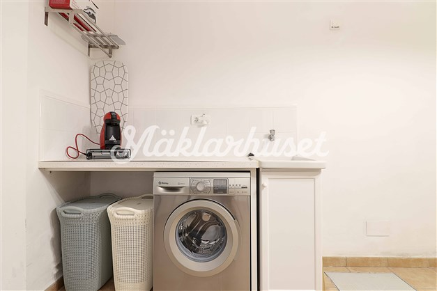 Tvätthörna i ett rum som även har gott om förvaringsplats.