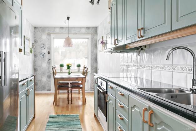Kök med fina materialval som rostfri kyl och frys, ny bänkskiva och häll.