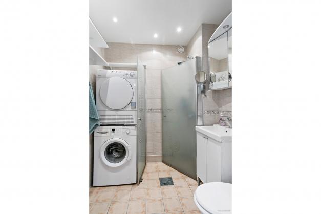 Helkaklat badrum med spottar i taket, tvättmaskin, torktumlare och duschhörn.