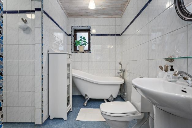 Rymligt badrum med badkar och dusch på övre plan