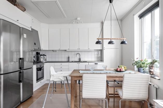Fullutrustat kök med maskiner i rostfritt. Vita köksluckor.
