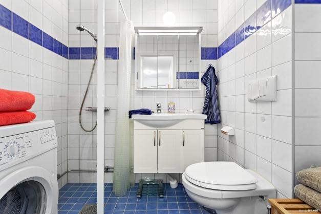 Helkaklat badrum med tvättmaskin.