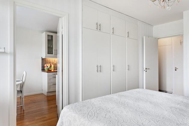 Sovrum intill balkong med praktiska inbyggda garderober mot ena långsidan.
