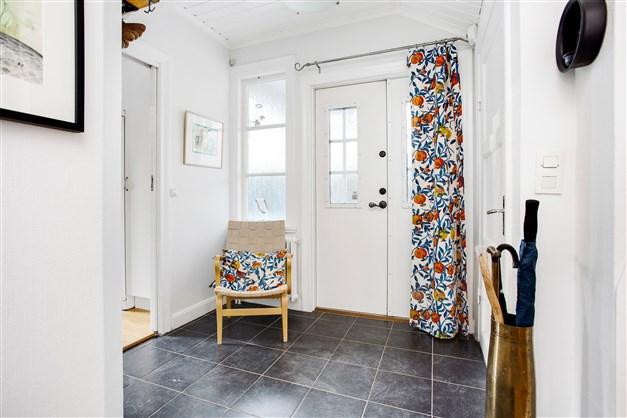 Ljus hall med nedgång till källare och uppgång till övervåningen.
