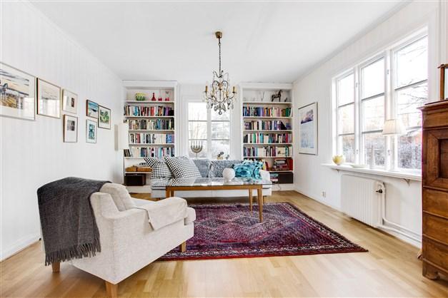 Vardagsrum med fin parkett och stora fönsterpartier.