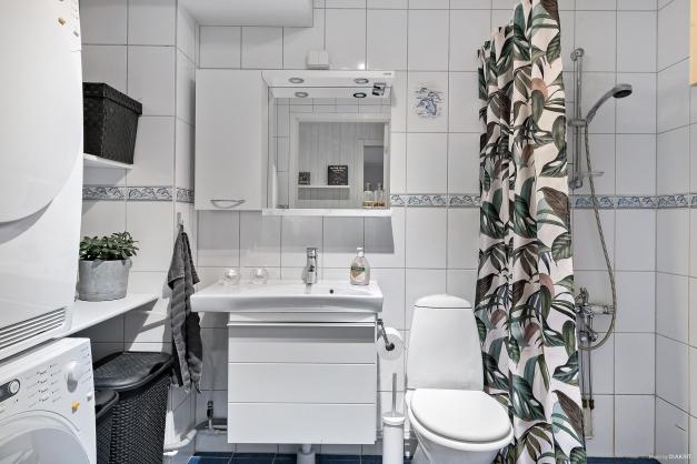 Helkaklat badrum från 2000 med plats för både tvätt och dusch.