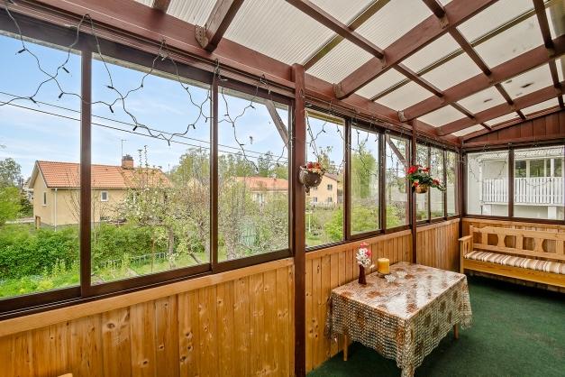 Den inglasade balkongen vetter in mot trädgården och har eftermiddags- och kvällssol