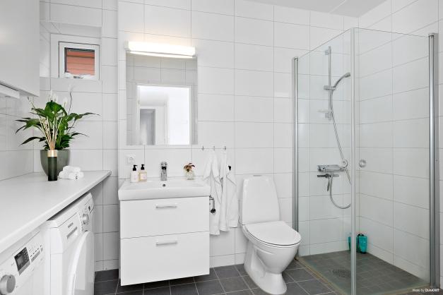 Stort helkaklat badrum med duschhörna med glasväggar. Inrett med handfat, WC, tvättmaskin och torktumlare samt litet gulligt fönster.