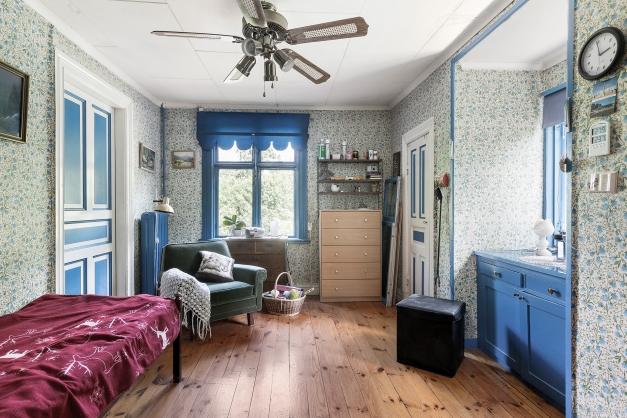Sovrum 1 med trägolv och platsbyggda garderober