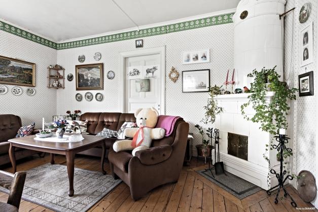 Salongen med trägolv och en vacker kakelugn