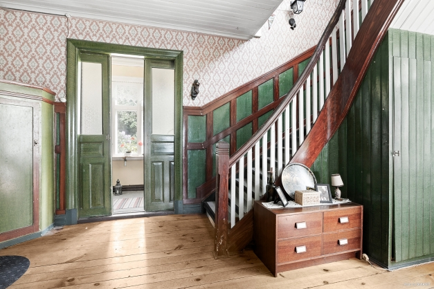 Entréhall med en vacker trappa till ovanplan och avhängning