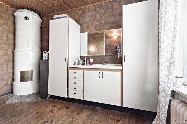 Ett av entréplanets rum har omvandlats till en stor toalett/dusch dem kakelugn (ej i bruk)