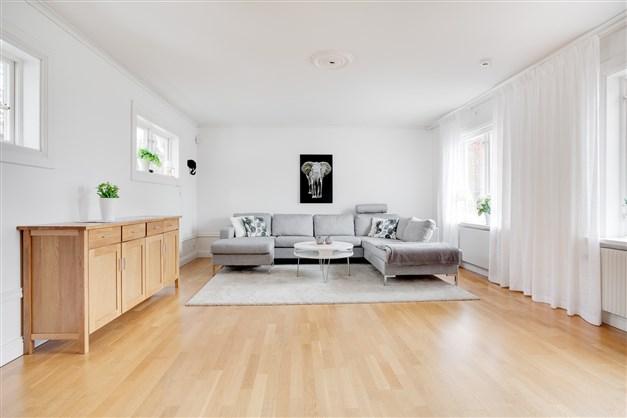 Ljust och fräscht vardagsrum med många fönster som tar in mycket ljus.