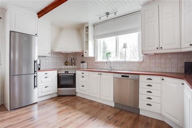 Köket är ljust med vit inredning och fönster vid arbetsbänken.