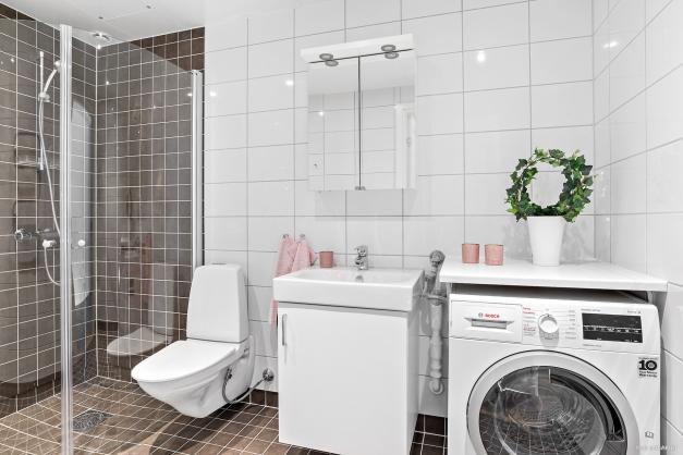 Snyggt badrum med kombinerad tvättmaskin/torktumlare