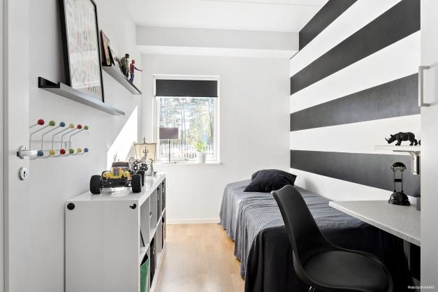 Sovrum med parkettgolv och garderob.