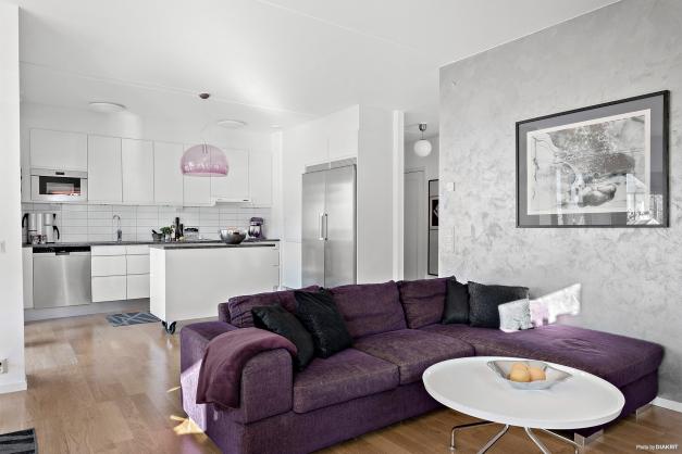 Öppen planlösning mellan kök och vardagsrum som har utrymme för både matplats och soffgrupp.