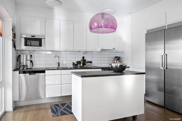 Välutrustat vitt kök från HTH med induktionshäll, fläkt, ugn, diskmaskin, micro samt kyl och frys.
