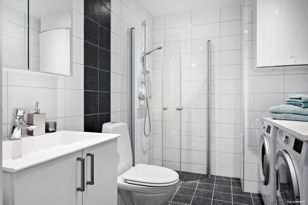 Det större, helkaklade badrummet är utrustat med handfat med kommod, wc, dusch, tvättmaskin och torktumlare samt komfortvärme i golvet.