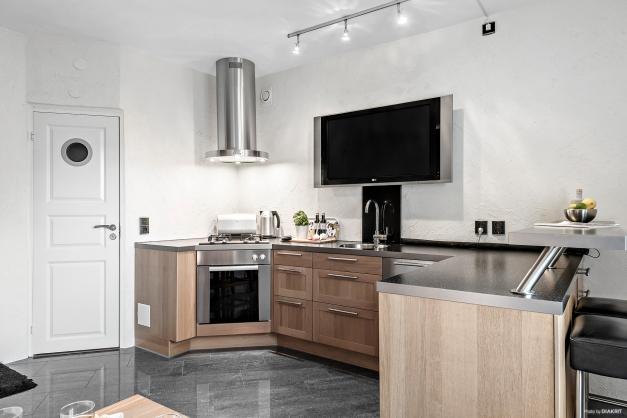 Stilrent kök med ugn, fläkt, diskmaskin, litet kylskåp och gashäll.