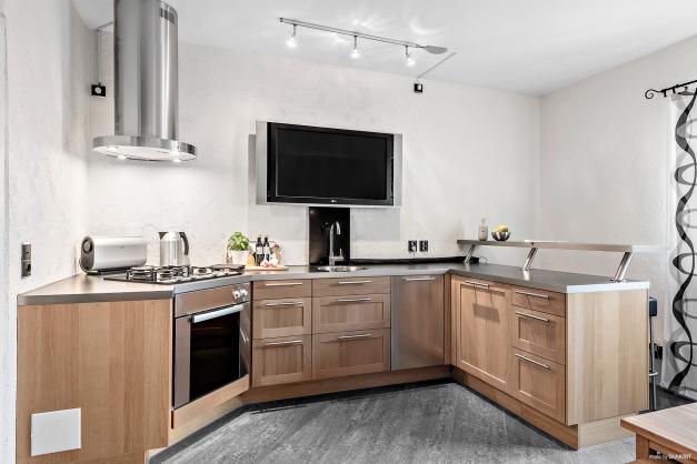 Köket har en sittplats vid bardisken, här sitter man gott med vännerna vid matlagningen. TV:n sitter på väggen, perfekt att ha en konsert igång eller kanske är det receptet vi finner där?