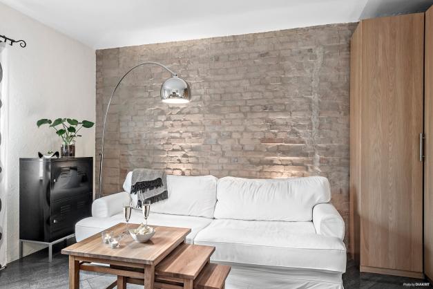 Soffhörnan som också blir sovavdelningen. Tegelväggen är vacker och ger fin färg till det övriga vitmålade och putsade ytorna.