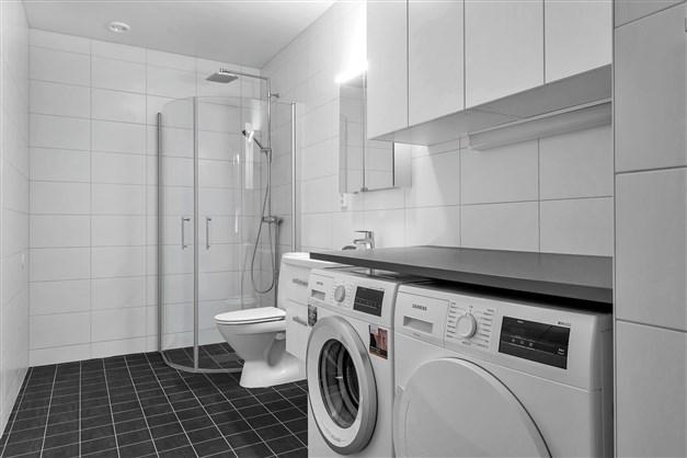Badrummet är inrett med handfatskommod med utdragbara lådor samt duschpaket med takdusch. Mörkgrått klinkergolv med komfortvärme. Vitt väggkakel. Tvättbänk med tvättmaskin och torktumlare. Överskåp med vita skåpluckor.