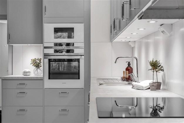 Lägenhet 1504 är tillvalsutrustad. Gråa köksluckor med svagt rundade kanter. Kyl och frys i rostfritt samt inbyggnadsmicro och inbyggnadsugn i rostfritt och vitt.