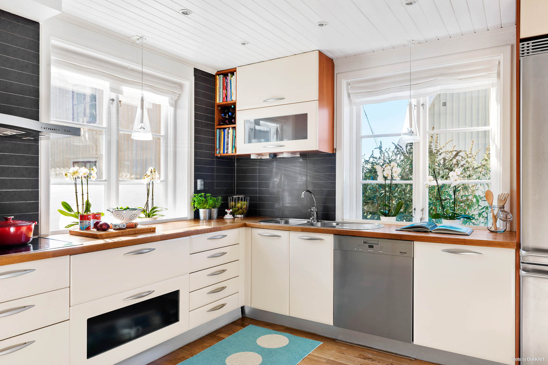 KÖK - Modernt kök med ljusa skåpluckor och stilfullt kakel och spotbelysning